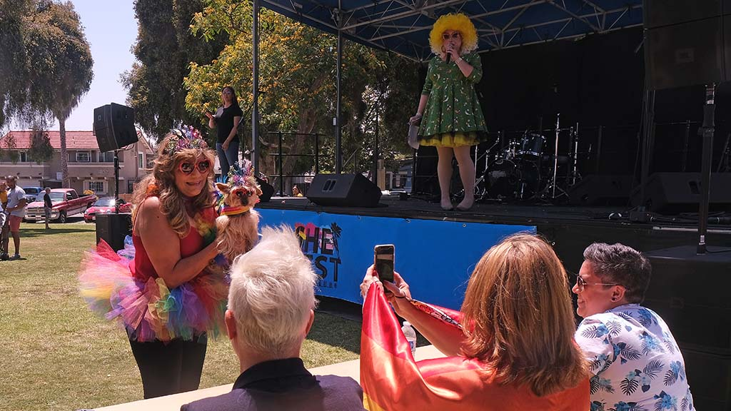 Mary Caraway of Poway shows off Bailey, a 14-year-old Yorkie, to the judges during the dog fashion competition at She Fest in North Park.