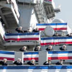 Sailors salute during commissioning of USS America