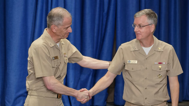 Rear Adm. Paul Pearigen congratulates Capt. Timothy Weber