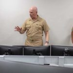 Adm. Christopher W. Grady (center) speaks with Rear Adm. Scott Robertson, commander, Naval Surface and Mine Warfighting Development Center (right) and Colvert Burgos, SMWDC's Surface Warfare Advanced Tactical Training Program Manager during a tour of SMWDC's Exercise Control Center at Naval Base San Diego.