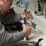 a plumber fixing a broken faucet