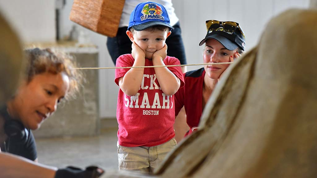 "Michael Oswald, 3, and his mother, Kristi of Hawaii watch sculptor Anique Kuizenga work on ""Think and Wonder, Wonder and Grow."" Photo by Chris Stone"