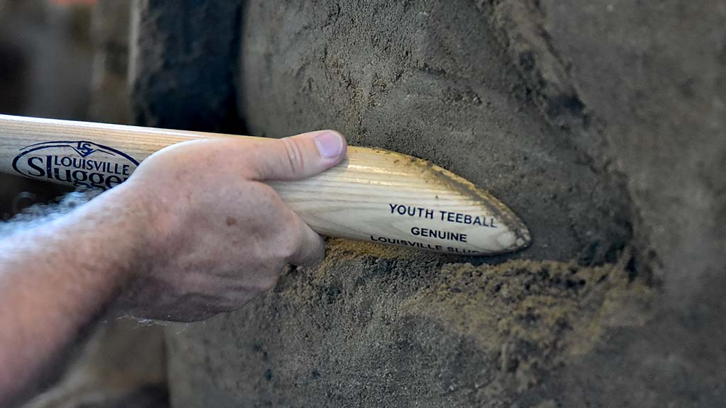 A sculptor uses a modified Louisville Slugger to smooth an area in an art piece. Photo by Chris Stone