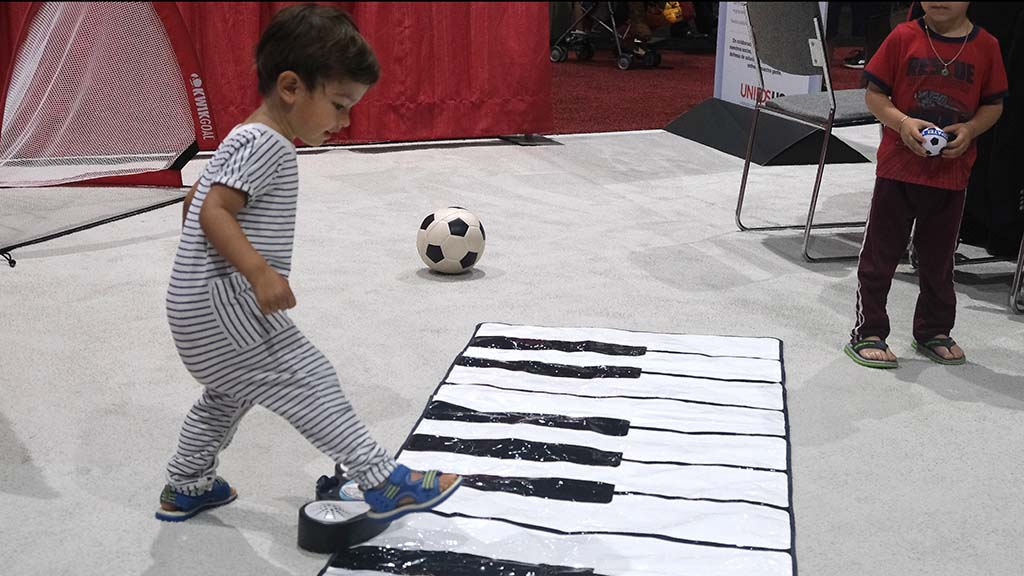 A 2-year-old boy delights in a musical keyboard at the National Latino Family Expo, held in conjunction with the UnidosUS annual Conference in San Diego.