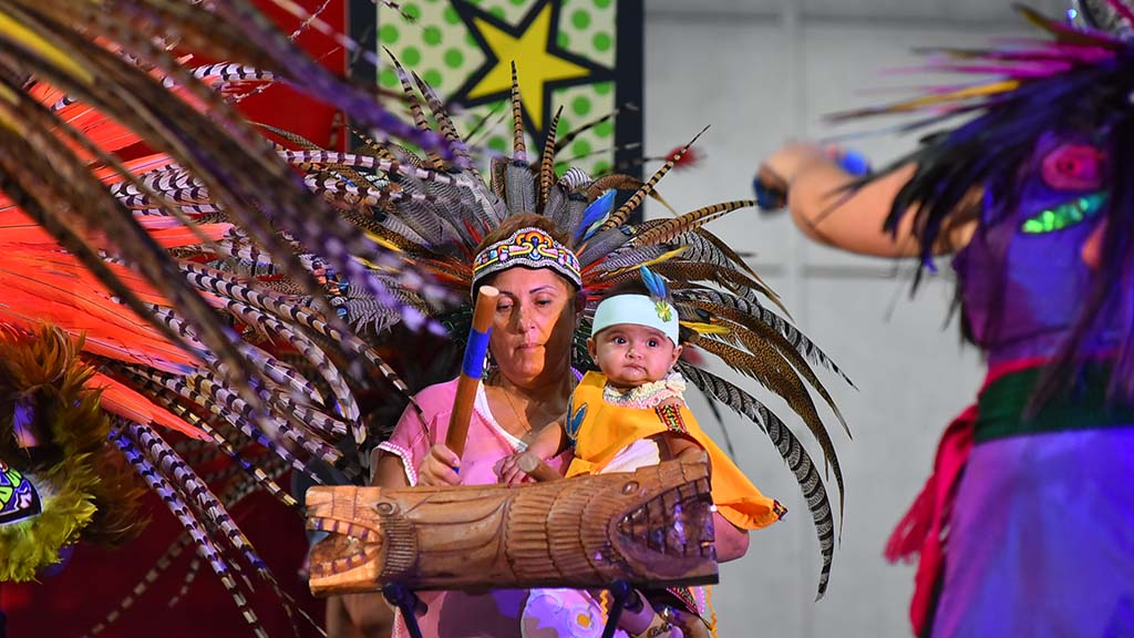 A woman drummer holding her grandson perform with The Mexi'cayotl Indio Culture Center Aztec dancers at the 2019 National Latino Expo. Photo by Chris Stone