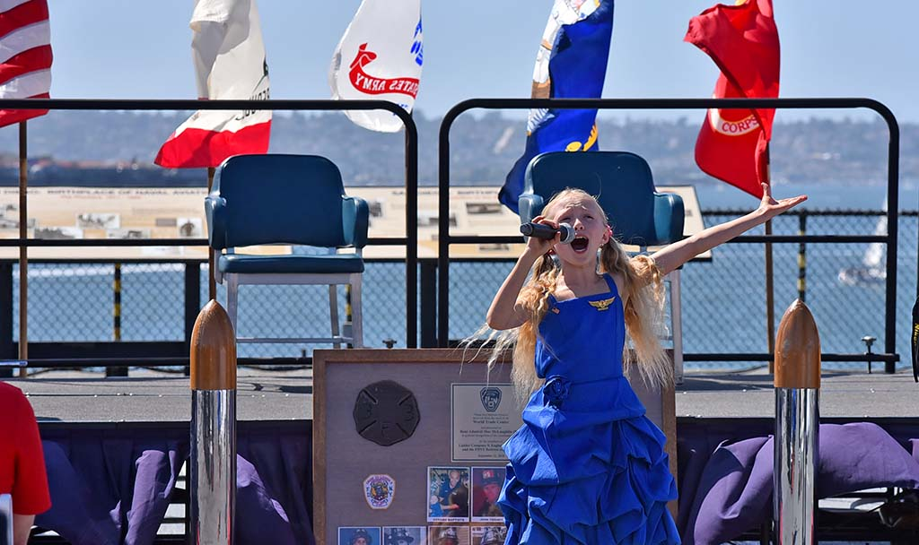 Sofia Brooks sang Good Bless America at the start of the 18th annual 9/11 USS Midway Memorial Service.