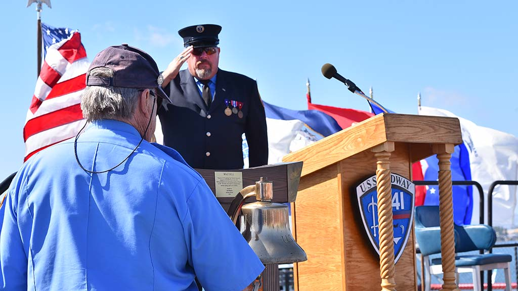 Retired New York Fire Fighter salutes after reading names of the fallen whileJerry Bresnan rings a bell. Photo by Chris Stone