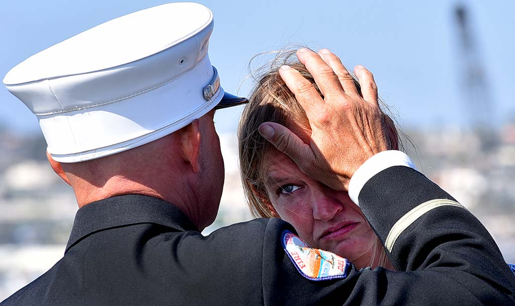A fire captain for the Del Mar Fire Department consoles a woman. Photo by Chris Stone