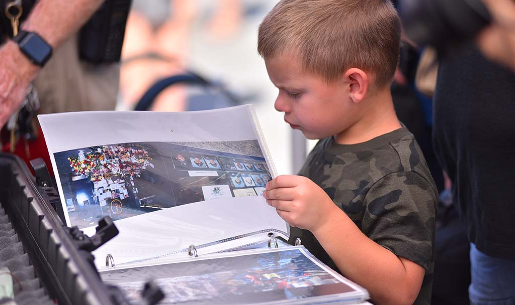A young boy looks through a book of photographs of the World Trade Center in 2001.