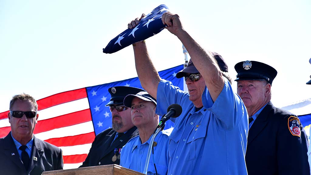 Jerry Bresnan, a retired New York fireman, holds a flag given to him by the U.S. Navy. Photo by Chris Stone