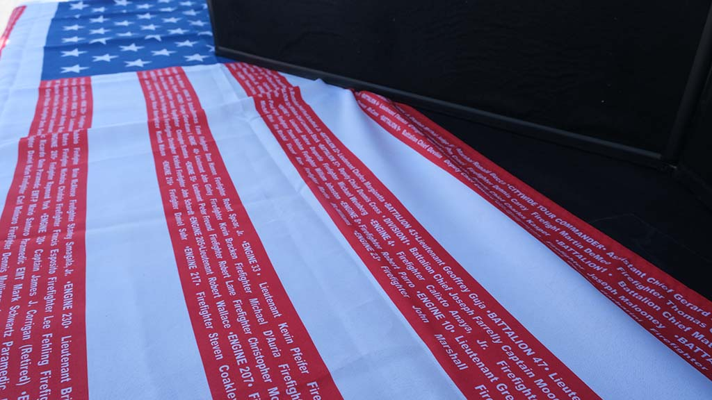 An American flag bearing the names of fallen firefighters was on display on the USS Midway for the 9/11 memorial. Photo by Chris Stone