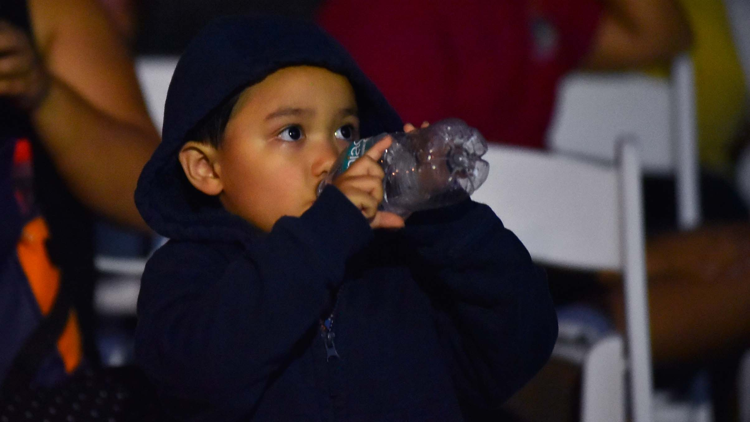"A young boy gets a drink as he eyes are glued to ""Captain Marvel."" Photo by Chris Stone"