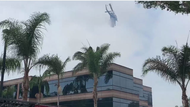 Helicopter drops water near a threatened building