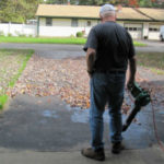 A man uses an electric leaf blower