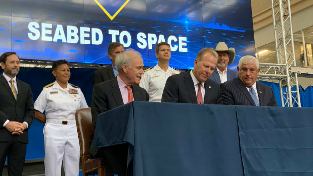 Navy Secretary Richard Spencer, Mayor Kevin Faulconer and SANDAG Executive Director Hasan Ikhrata sign the agreement.