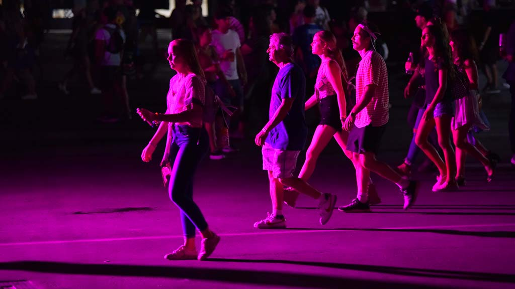 Purple light bathes attendees as they travel from concert to concert.