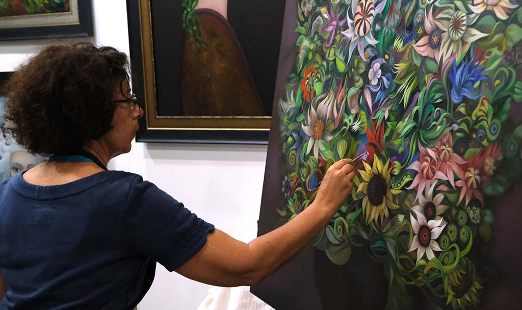 Artist Alla Tsank puts finishing touches on her parting in exhibit hall at KAABOO Del Mar.