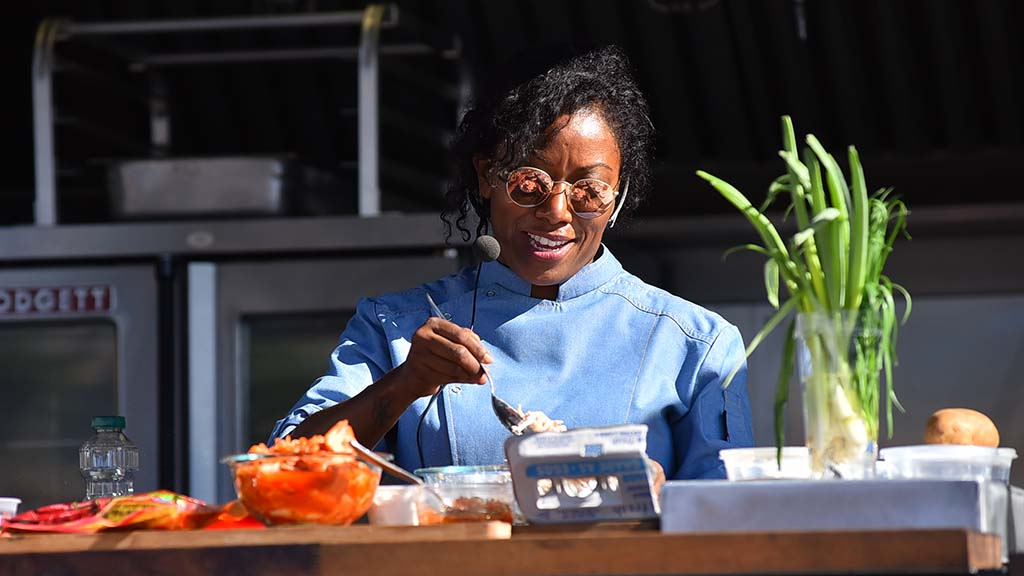 Nyesha J. Arrington prepared to make latkes for attendees gathered at her cooking station.