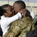 Military spouse hugs returning service member