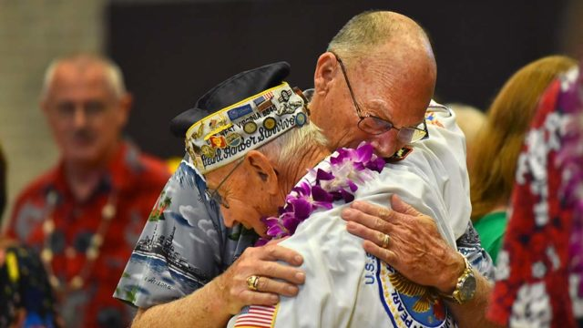 Jack Evans Jr., son of the late vice president of the group, embraces Pearl Harbor survivor Stu Hedley after the final meeting, the last in the nation.