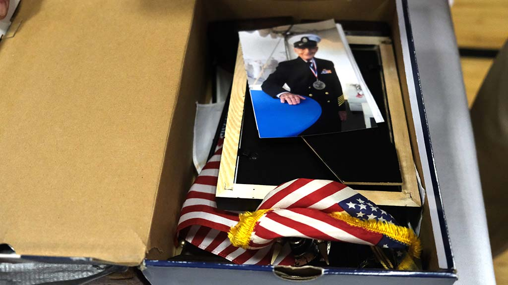 Pearl Harbor survivor Stu Hedley packed up association meeting belongings, including a photo of himself while in active duty.
