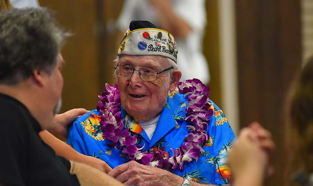 Pearl Harbor survivor Clayton Schenkelberg, 101, speaks to his son Patrick at the meeting.