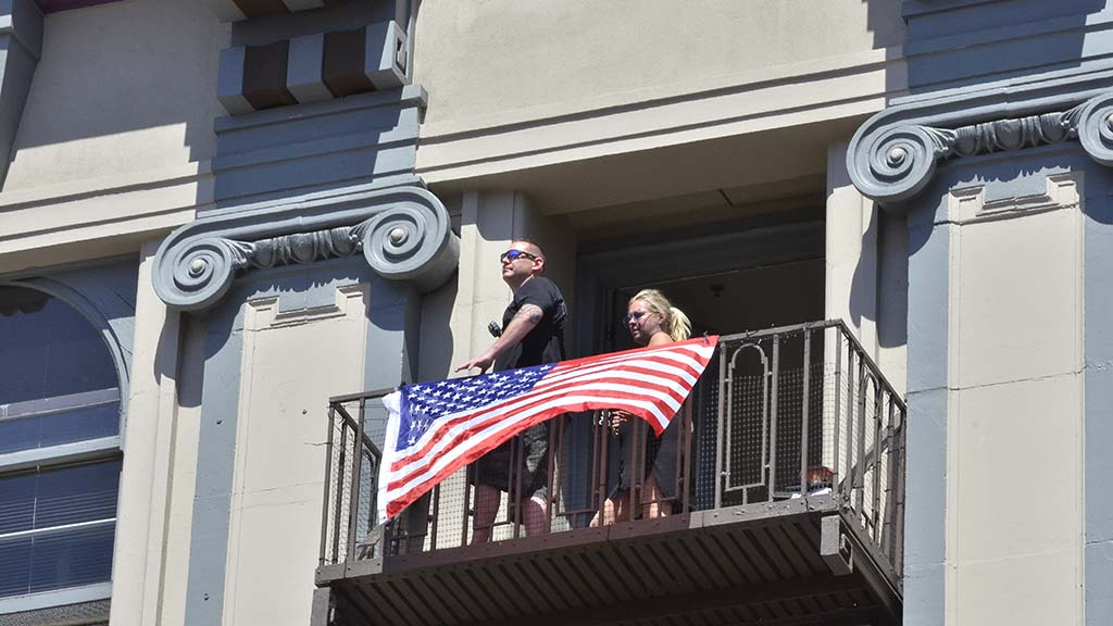 A couple displays a flag in a building next to the Grant Hotel where the president spoke.