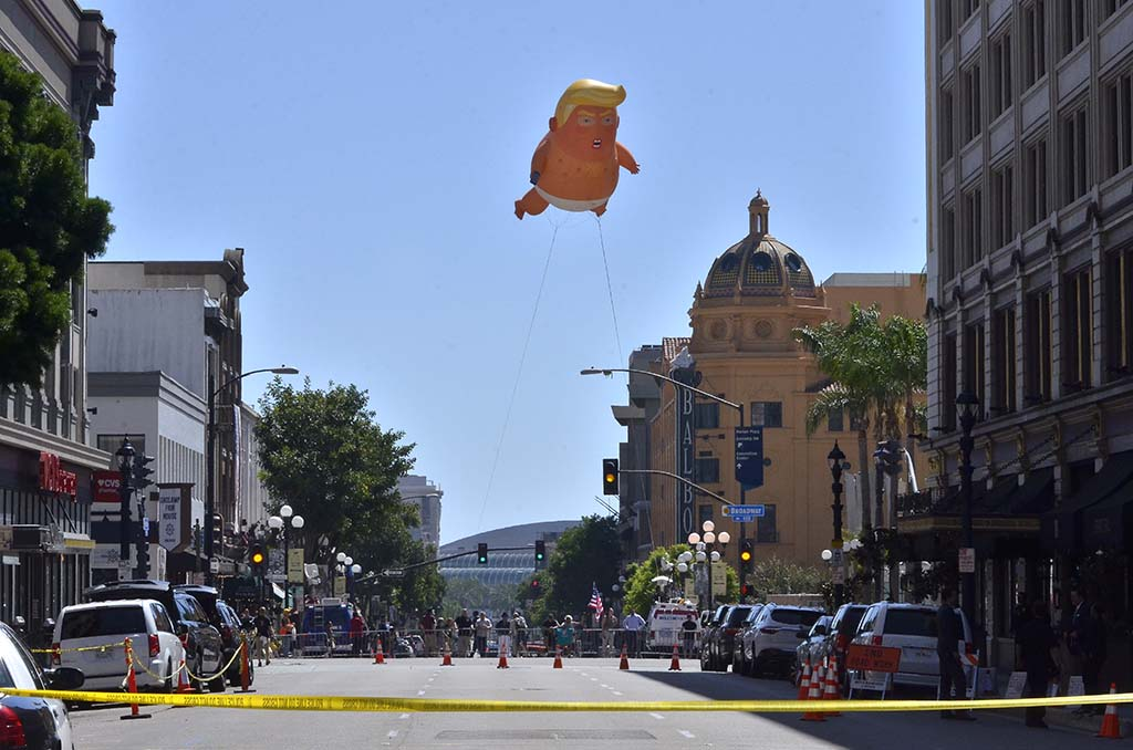 A baby Trump balloon floats near the U.S. Grant Hotel, where the president speaks at a fundraiser.