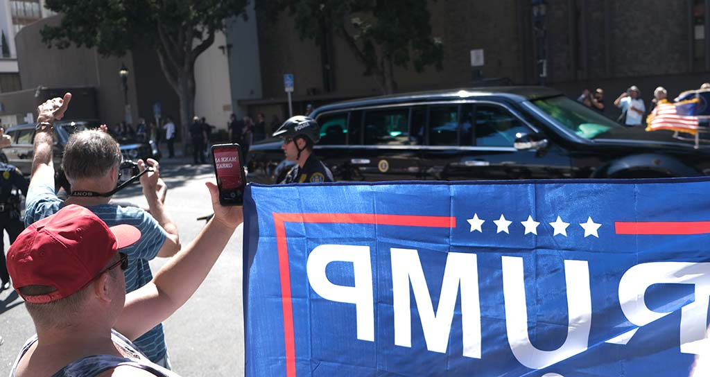 Trump fans hold up a campaign sign as the presidential motorcade passes in downtown San Diego.