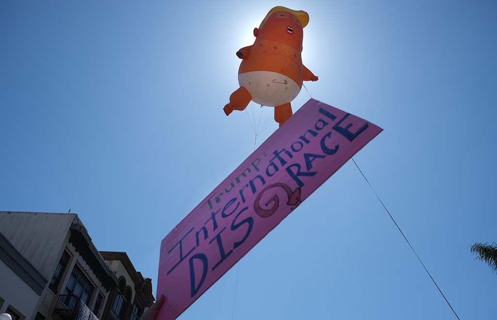 As a protester holds a sign, a baby Trump balloon is flown across the street from the U.S. Grant Hotel.