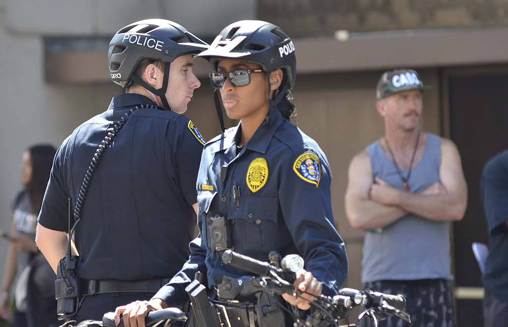 San Diego officers watch the crowd along the motorcade route as supporters and protesters exchange jabs.