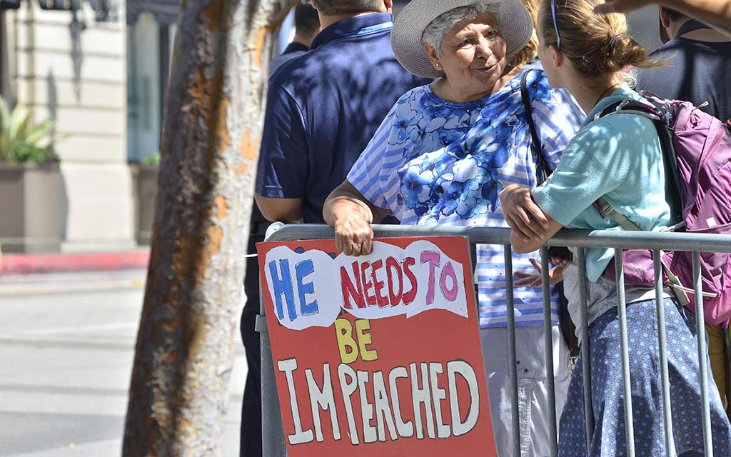 A woman protesting the president's visit i San Diego waits across the street from the Grant Hotel, where Trump spoke.