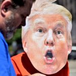 A woman who declined to give her name wears a Donald Trump mask to a protest near where he was speaking.