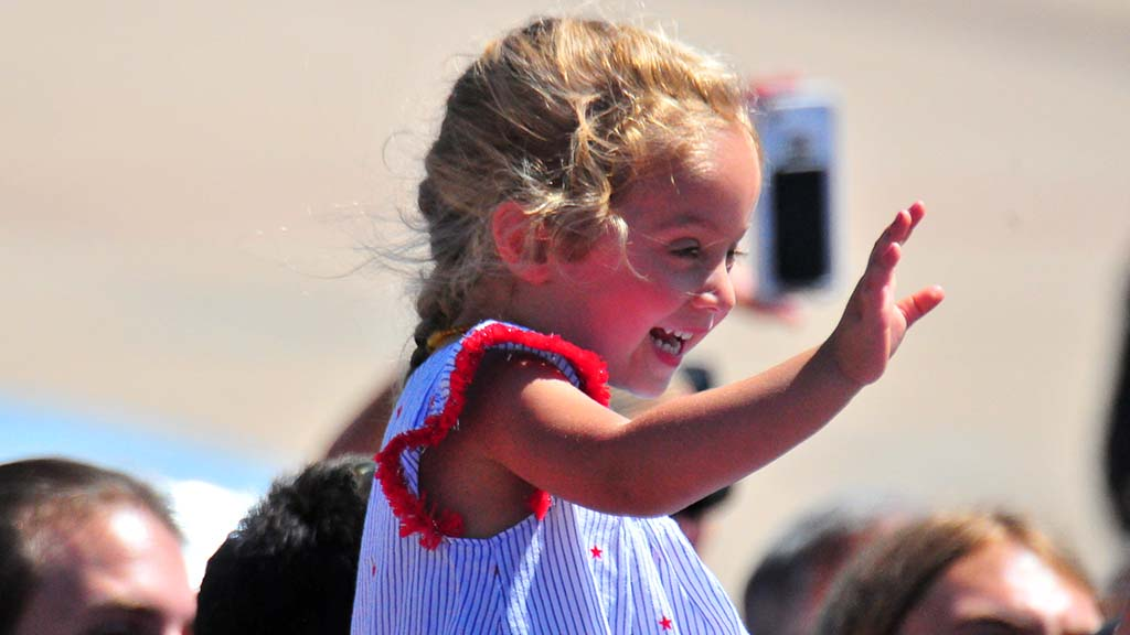 A little girl waves goodbye to President Trump during his 10-minute visit to Marine Corps Air Station Miramar.