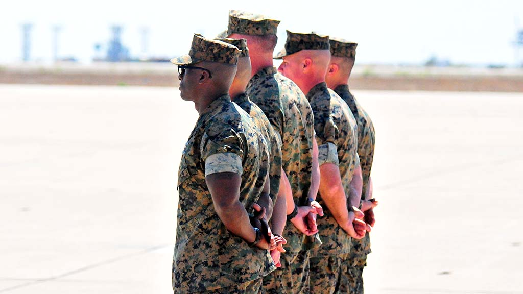 Marines stand at ease on flight line as President Trump nears end of Miramar visit.
