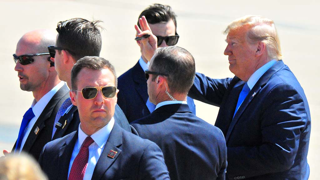 Holding a pen and surrounded by Secret Service team members, President Trump signals farewell to crowd.