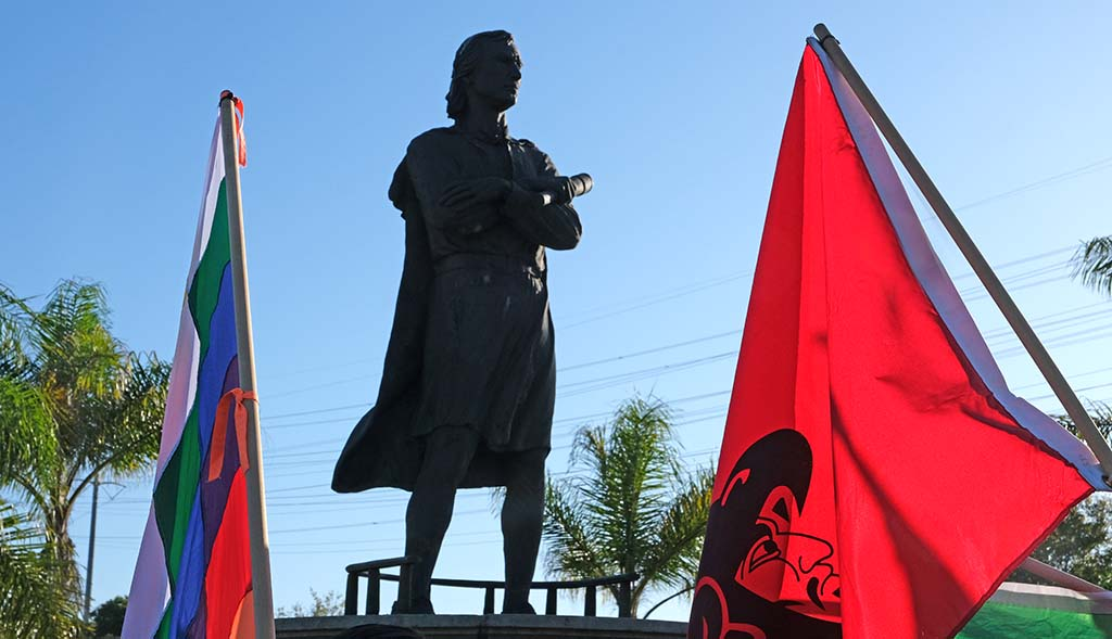 Flags of groups calling for the removal of the Christopher Columbus statue flank it.