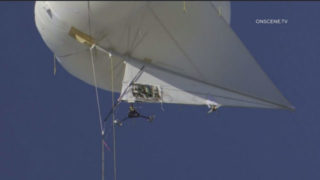 Drone hovers below tethered balloon