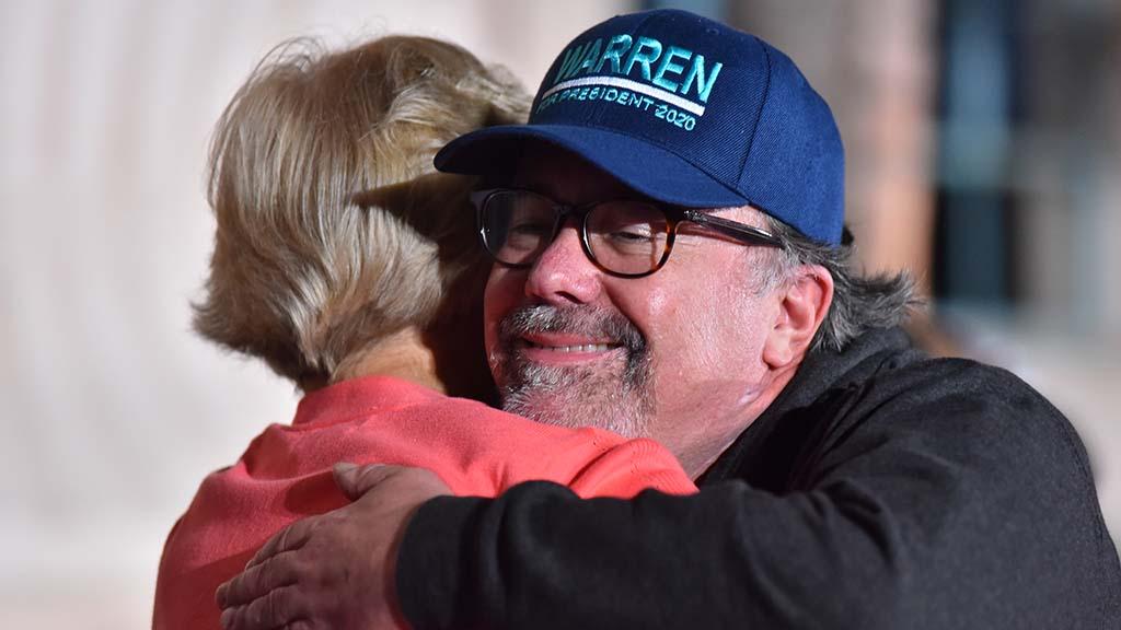 Wearing a hat (among many branded items on sale on a nearby sidewalk), an Elizabeth Warren fan gets a hug