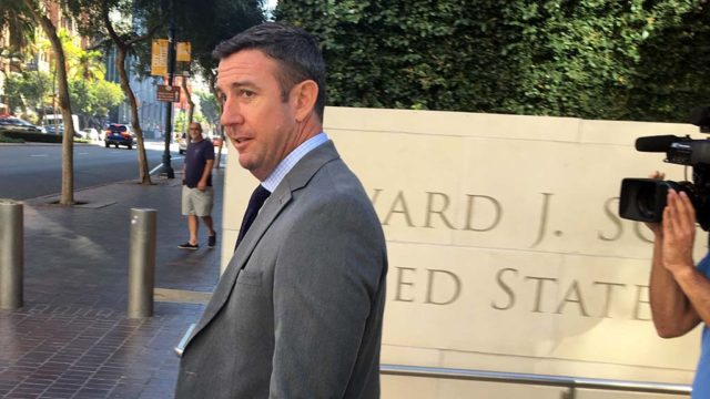 Trailed by news cameras but no protesters, Rep. Duncan D. Hunter leaves federal court after agreeing to new trial date.