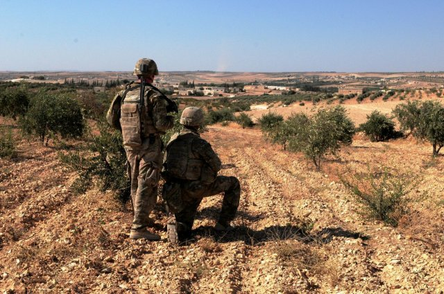 U.S. Army soldiers observe Turkish forces in the distance during a patrol outside Manbij, Syria