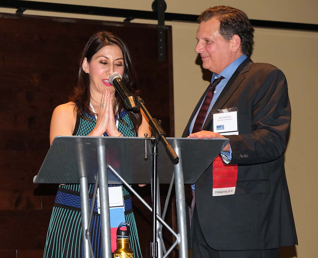 Bob Stefanko and niece Mia Park, of Ranch & Coast Magazine accept Jim Reiman Award for excellence in media management.