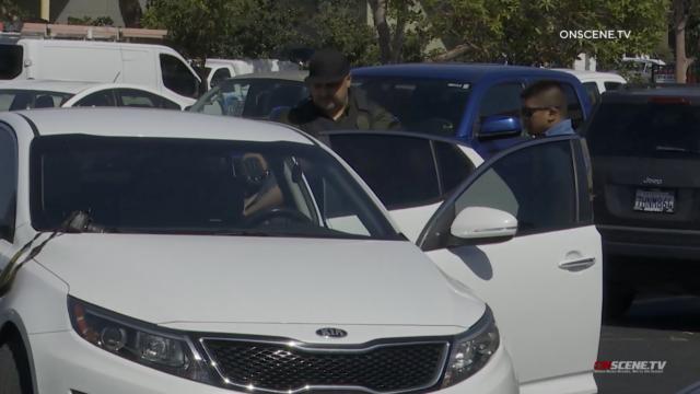 Authorities put suspect in car.