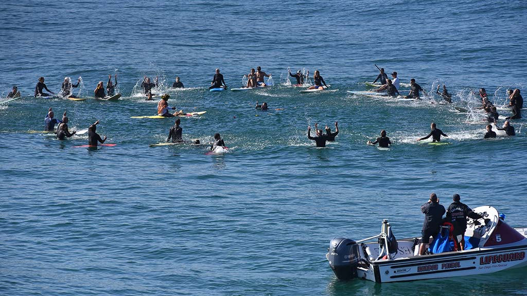 Paddle out participants slap the ocean water as a tribute to ocean scientist Walter Munk on Saturday.