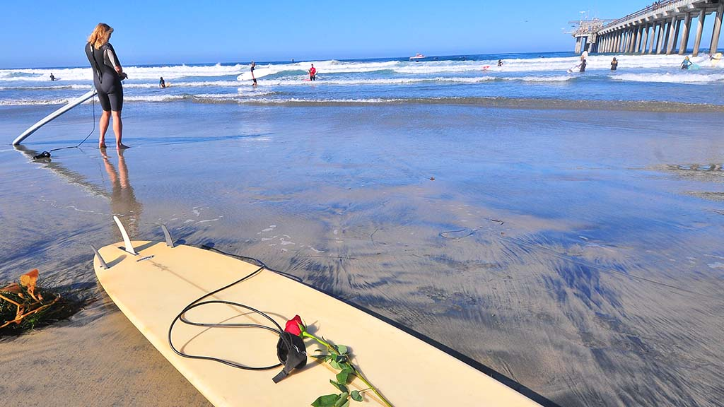A red rose for the paddle out is placed on a s