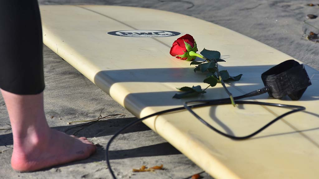 A red rose for the paddle out is placed on a surfboard was surfers prepare.