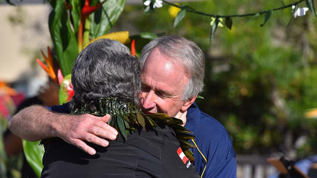 Byron Washom, a UC San Diego executive, hugs widow Mary Coakley Munk, after an emotional tribute.