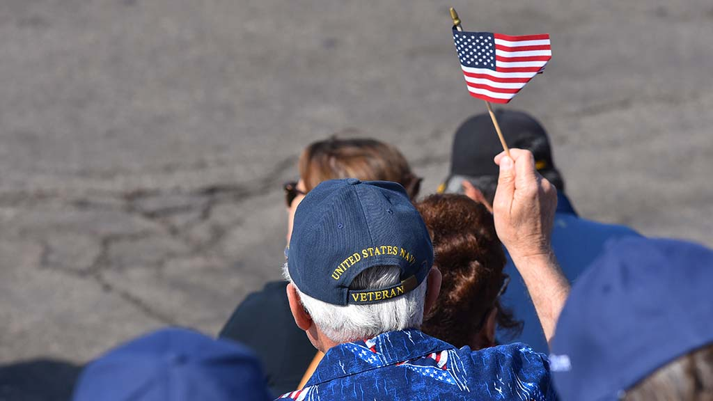 A veteran waves his flag as parade participants pass.