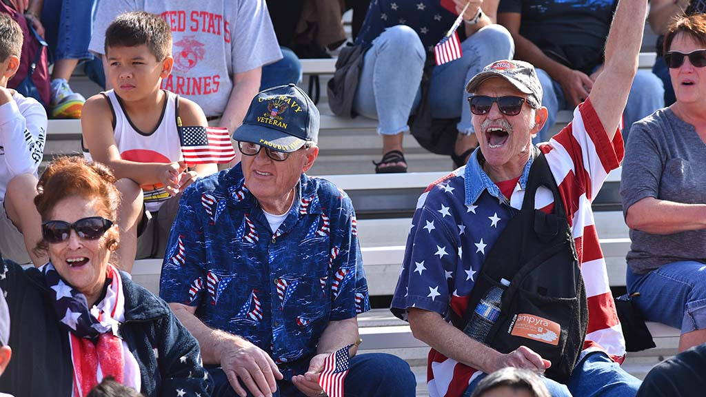 Veterans sitting in temporary stands by Waterfront Park cheer as military units pass