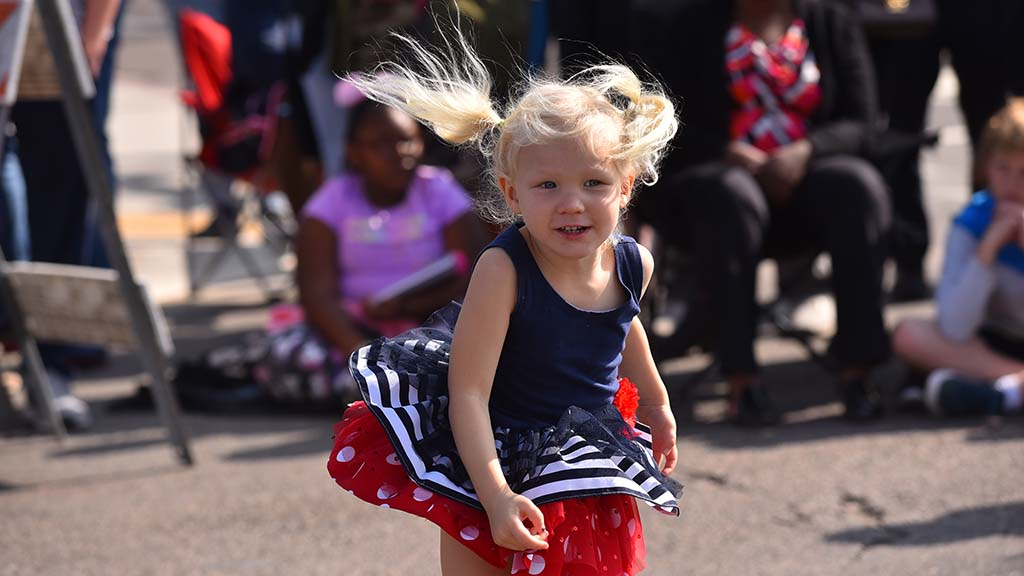 Madeline Herschelman, 3, whose grandfather is marching in the parade, twirls to band music.